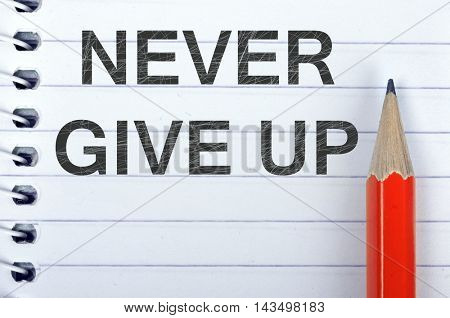 Never give up text on notepad and red pencil