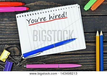 You're hired text on notepad and office tools on wooden table