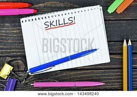 Skills text on notepad and office tools on wooden table