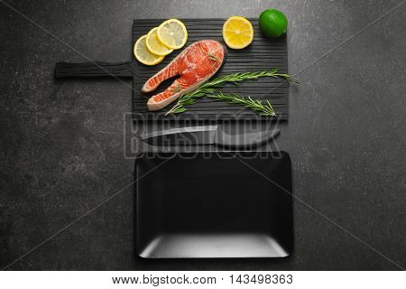 Red fish, lemon and rosemary on black textured background