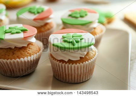 Tasty cupcakes with clover on plate. Saint Patrics Day concept