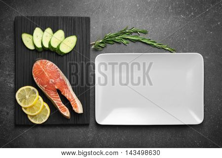 Red fish and ingredients on black textured background