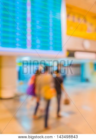 Blur Image Of Blue Screen Flight Schedules And People In Airport.