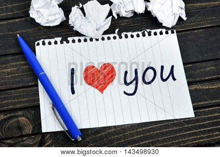 I love you text on notepad and crippled paper