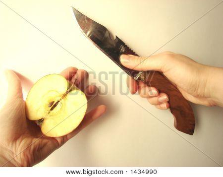 Closeup Of Hands Holding A Cut Apple & Sharp  Knife