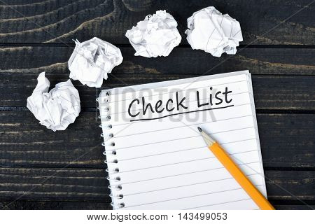 Check list on notepad and crippled paper