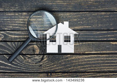Magnifying glass paper house on wooden table