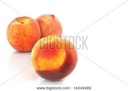 Three luscious ripe peaches, on reflective white surface.