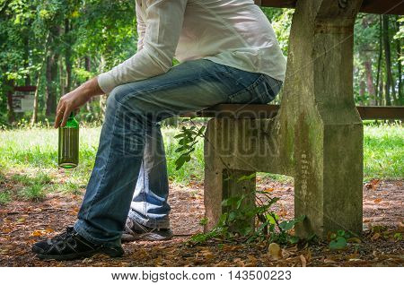 Lonely Drunk Man With Beer Bottle Sitting On Bench