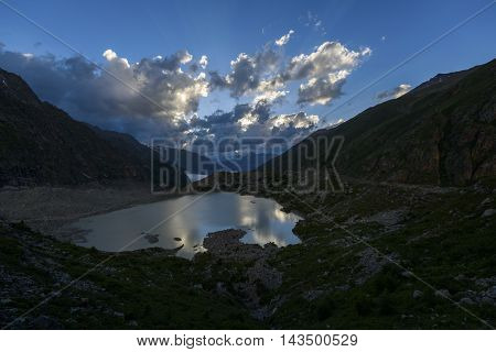 the glacial lake in beams of the sunset sun against cloudy mountains