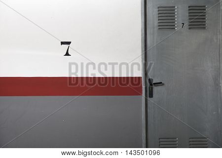 Grey door and painted wall in greywhite and red lines with number seven