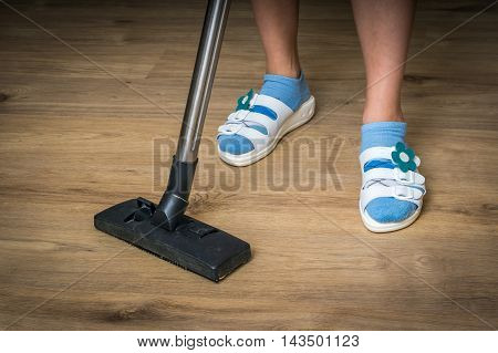 Woman With Vacuum Cleaner Cleaning Wooden Laminate Floor