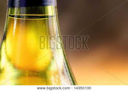Closeup of a cold bottle of white wine, with golden natural light background.