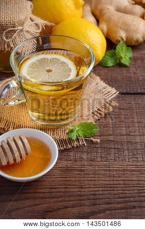 Ginger root tea with lemon and honey on wooden background, selective focus, copy space