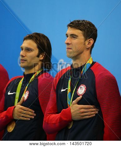 RIO DE JANEIRO, BRAZIL - AUGUST 13, 2016: USA Men's 4x100m medley relay team  Cory Miller (L) and  Michael Phelps celebrate victory at the Rio 2016 Olympic Games at the Olympic Aquatics Stadium