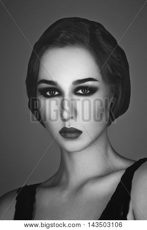 Beautiful young woman with smoky eyes and full red lips. Studio beauty shot. Copy space. Monochrome. Retro styling.