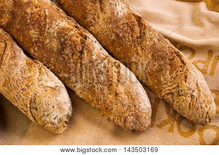 Fresh home baked Alpine Baguettes with Pumpkin Sesame Chia Flax Seeds cereal flakes and rye sourdough starter on cotton napkin. Healthy food concept.