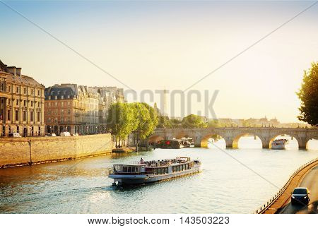 Pont Neuf and Seine river with tour boat at sunny summer sunset, Paris, France, toned