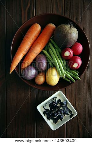 Plate with fresh vegetables and sauce in bowl on wooden background