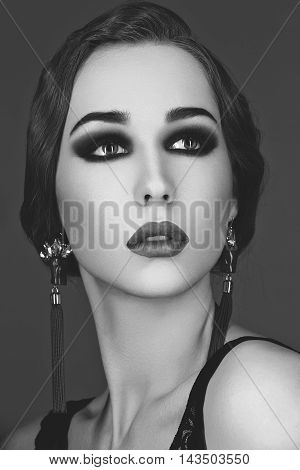 Beautiful young woman with smoky eyes and full red lips. Studio beauty shot over dark background. Copy space. Monochrome.