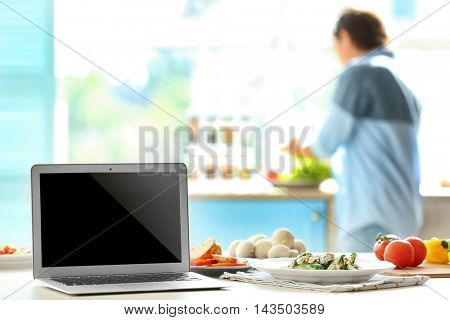 Laptop on kitchen table and cooking girl. Food blogger concept