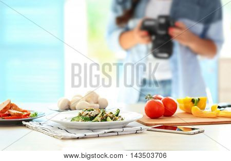 Plate with salad on table and girl photographing at kitchen. Food blogger concept