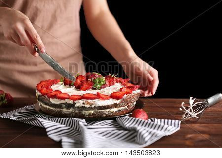 Woman slicing appetizing cake decorated with strawberry