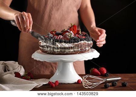 Woman decorating sweet fruitcake with cream