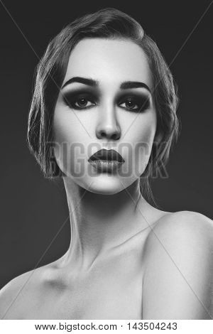 Beautiful young woman with smoky eyes and full red lips. Studio beauty shot. Copy space.