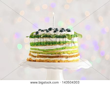 Delicious cake on stand on light background