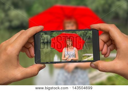 Woman hands with mobile cell phone to take a photo of young lady with red umbrella near the pond