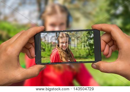Woman hands with mobile cell phone to take a photo of young lady listening to music and relaxing on a park bench