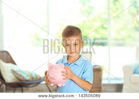 Savings concept. Cute boy holding piggy bank