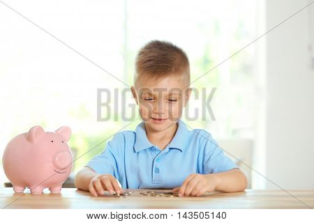 Savings concept. Little boy counting coins at table with piggy bank