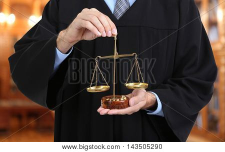 Judge holding scales blurred view of books