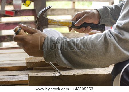 Carpenter using  chisel and hammer in his hand with plank.Close up and stillife.0002