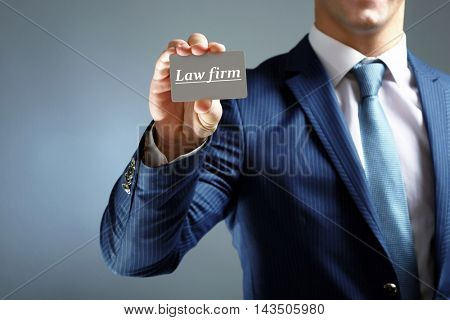 Elegant man in suit holding business card LAW FIRM