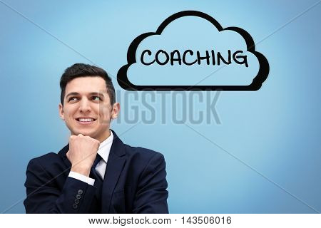 Personal coaching concept. Attractive young man in a suit against light blue wall