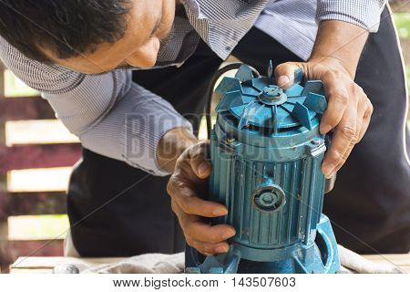 Electric motor  and man working equipment repair on wooden floor background.Background mechanic or equipment.Zoom in