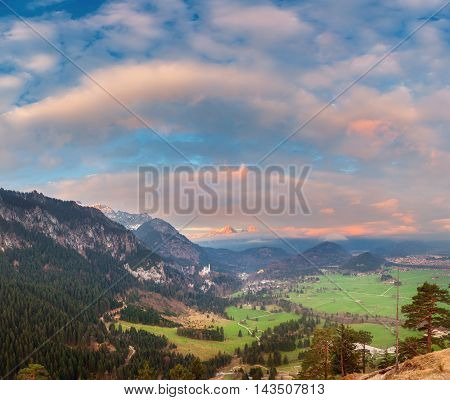 Beautiful colorful panoramic landscape with alpine mountains trees green meadow clouds and blue sky at sunrise in spring. Alps in Germany