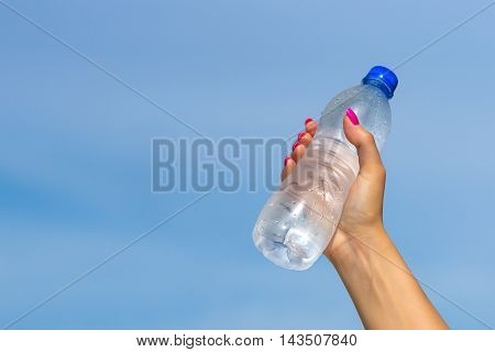 Woman hand holding water bottle outdoors in sky background