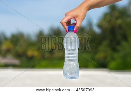 Woman hand holding water bottle outdoors  in nature background