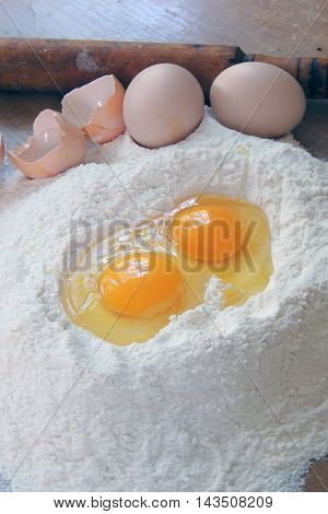 Eggs rolling pin and flour closeup .