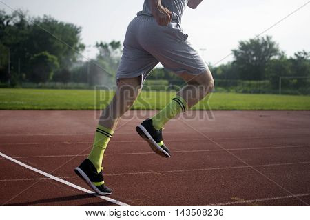 The runner is starting to run at the stadium.