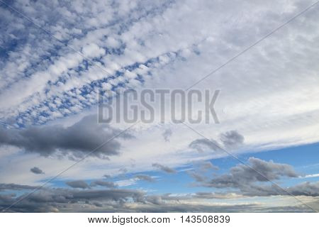 Beautiful summer cloudscape as gray and white clouds fan across a blue sky