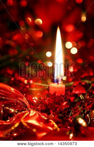 Red Christmas candle amidst decorations and defocussed lights.