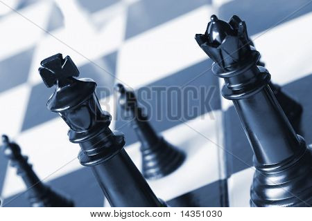 Chess pieces in blue duotone.  Focus on black king and queen.