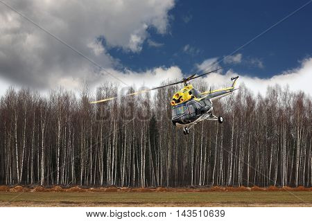 Aircraft - Big black-yellow helicopter at competitions makes flight at low height on cloudy sky background.