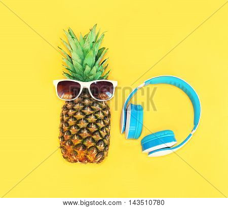 Fashion Pineapple With Sunglasses And Headphones Over Colorful Yellow Background