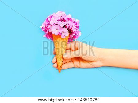 Hand Holding Ice Cream Cone With Flowers Over Blue Background